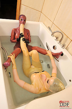 Latex beauties enjoy playing a game of footsies in the tub