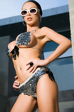 Nikki Benz exudes that Old Hollywood screen diva sex appeal as she struts around and fools around with herself in a flowing scarf/headwrap, silver sequined swimsuit and ropes of pearls and gold bling!